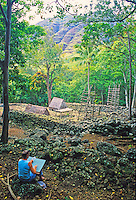 The Kaneaki Heiau. Located in Makaha Valley near Oahu's leeward coast. A woman artist sketches the Heiau.