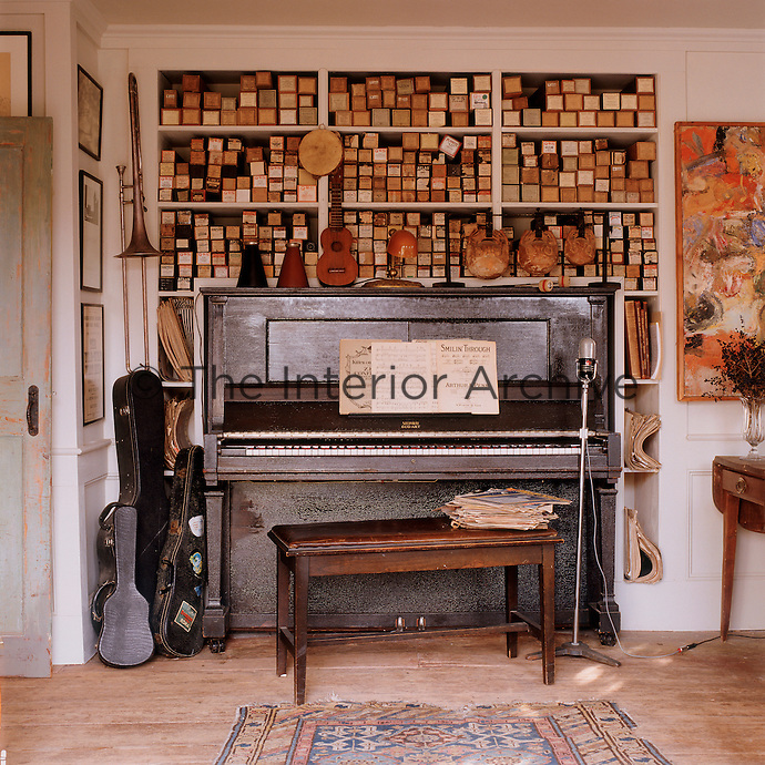 The music room is graced with a 1925 Steinway player piano and is surrounded by a collection of musical instruments and shelves stocked with 1920s piano rolls