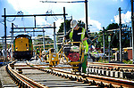 UTRECHT - Op het Centraaal Station in Utrecht draait een medewerker van BAM Rails het nieuwe spoor vast tijdens het aansluiten van het bestaande spoornet aan de nieuwe sporen bij Lunetten. In opdracht van ProRail is het treinverkeer tussen Utrecht en Den Bosch vanaf vrijdagavond tot stopgezet om oud spoor op te breken, ballast te storten en nieuw spoor aan te sluiten. De werkzaamheden horen bij de uitbreiding van het Utrechtse spoor waarbij 80 kilometer nieuw spoor en7 nieuwe stations verrijzen die ondermeer nodig zijn voor het bouw van het regionale spoornet Randstadspoor. Nadat het spoor werd vastgezet, kwam de ballasttrein (links) om de rails vast te zetten. COPYRIGHT TON BORSBOOM
