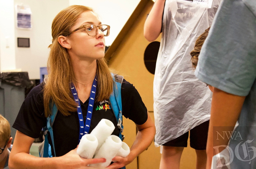 NWA Democrat-Gazette/ELIZABETH GREEN Cami Hedstrom, a senior at the University of Arkansas at Fort Smith and an intern for the Amazeum, helps children with paint Wednesday, June 26, 2019 during one of the museum's summer camps.