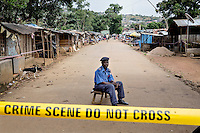 Police sergeant Alimamy Kamara, 53, on guard duty in the village of Grafton where 47 households on the main street have been put into quarantine after at least 17 cases of ebola were reported. Officially no one is allowed to enter or leave the houses, but in reality the quarantine is far from strict and villagers can easily leave their houses through their backdoors.