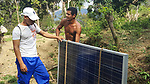 Our guide, Juan Luis inspects a solar panel that Rosita's husband hauled up the mountain on his back.  He told us the panels were issued by the Cuban government and they pay a low monthly rent.  Once installed, they will have lights for the first time.