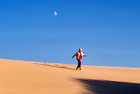 Child running down sand dune. Near Florence, Oregon.