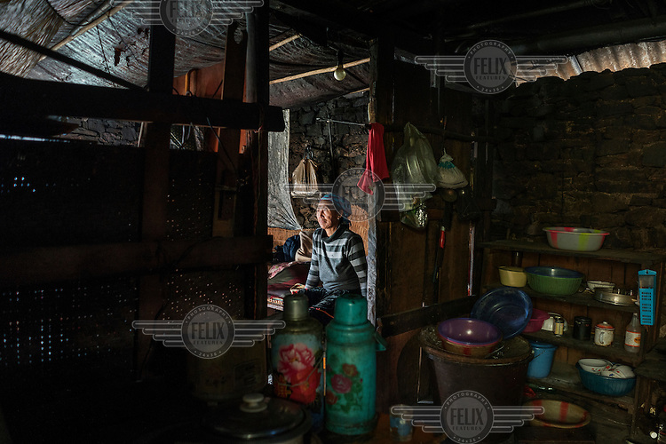 Naye Bu, 60, a Lisu villager sits in the home, above the bank of the Nujiang River, she has shared with her husband for 30 years.