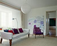 The colours in the large painting by Patrick Heron are reflected in the purple chair and colourful cushions in this living room