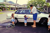 Father and children outside washing the family car