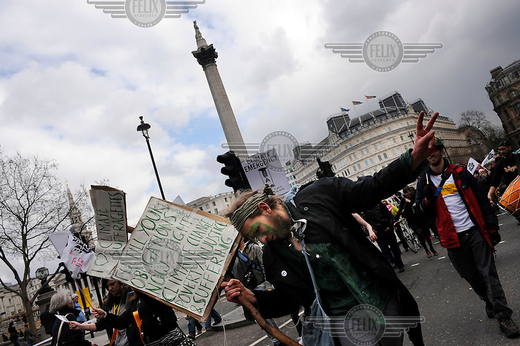 A marcher carries a placard about climate change through Trafalgar Square during the Put People First protest. It was the first of a series of demonstrations in London ahead of the G20 summit of world leaders to express anger at the economic crisis, which many blame on the excesses of capitalism.