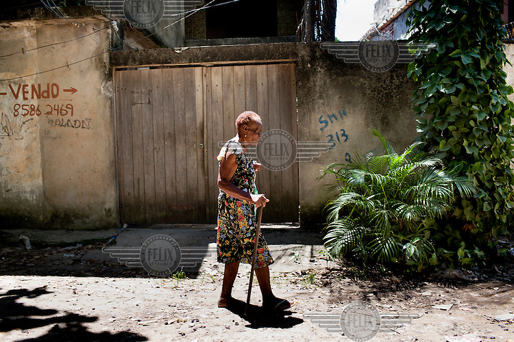 An elderly woman walks past a home that is marked for eviction in the favela community of Vila Autodromo, where nearly 3000 families have been evicted from their homes and relocated to far away neighbourhoods. More then half of the families did not want to leave.