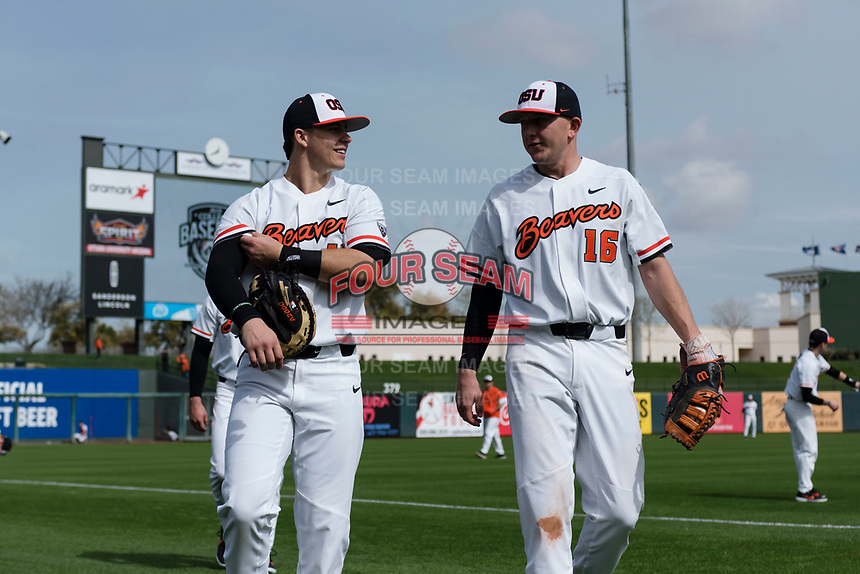 Oregon State Beavers catchers Troy Claunch (17) and Zak Taylor (16) warm up before a game against the New Mexico Lobos on February 15, 2019 at Surprise Stadium in Surprise, Arizona. Oregon State defeated New Mexico 6-5. (Zachary Lucy/Four Seam Images)