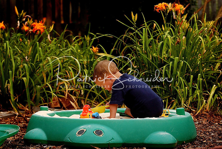 A toddler enjoys his afternoon sifting sand in his backyard sandbox.