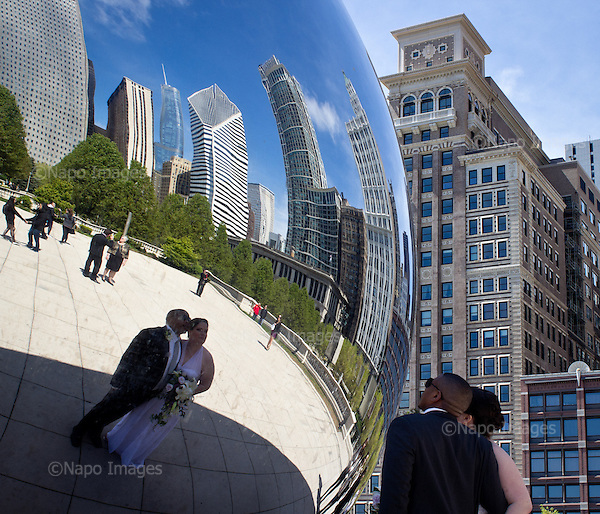 "CHICAGO, ILLINOIS, USA 22 APRIL, 2012:.Newlyweds are looking at their reflection by the famous ""Bean"" sculpture in Millenium Park in centre of the town..(Photo by Piotr Malecki / Napo Images)..CHICAGO, ILLINOIS, USA 22/04,2012:.Nowozency przegladaja sie w powierzchni slawnej rzezby ""bean"" (fasolka) w Millenium Park w centrum miasta..Fot: Piotr Malecki / Napo Images"