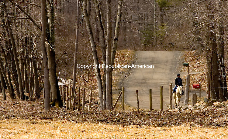 SOUTHBURY, CT--11 MARCH 2007--031107JS01- A woman rides her horse past Phillips Farm in Southbury. FOR COUNTRY LIFE<br /> Jim Shannon / Republican-American