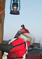 Glenn Lockwood, the last musher to Nome preparing to extinguish the light.