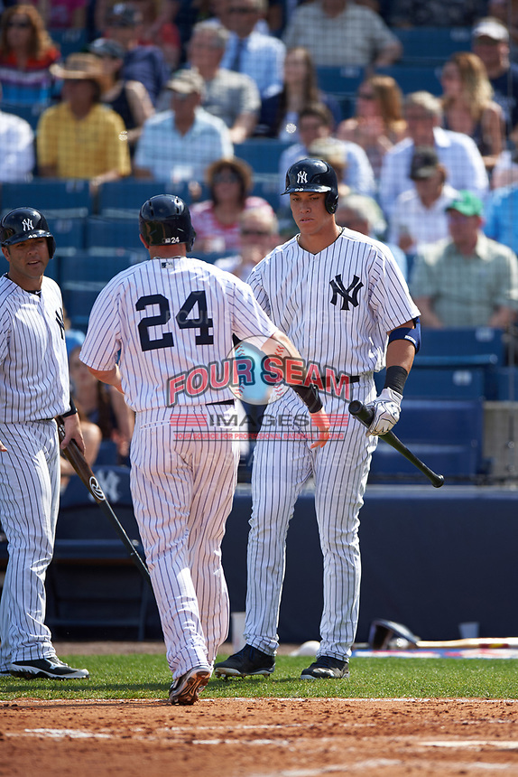 New York Yankees Dustin Ackley (29) shakes hands with Aaron Judge (99) as Austin Romine (left) looks on during a Spring Training game against the Detroit Tigers on March 2, 2016 at George M. Steinbrenner Field in Tampa, Florida.  New York defeated Detroit 10-9.  (Mike Janes/Four Seam Images)