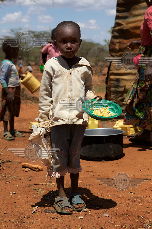 Children gather to receive their lunch from a tin roof kitchen in Emengan Primary school, Isiolo, West Kenya.