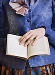 A closeup of a victorian lady in a decorative outfit, holding a book, with her left hand touching the page of the book in a delicate manner.