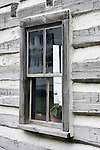 historical log cabin window building logcabin structure old past long ago 150 years historic deterioration aging fashioned glass wood recycle build by hand home house farm settlement settle memories united states west time plaster construction material