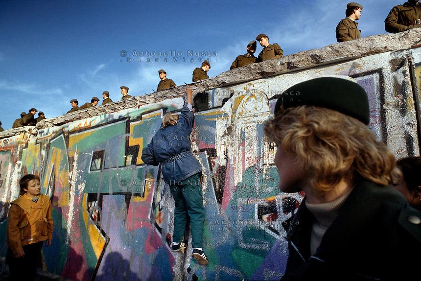 Berlino, 9 Novembre, 1989. Un bambino si arrampica sul muro di Berlino presidiato da soldati della Germania dell'Est poco prima della sua caduta.A youth climbs the Berlin wall.