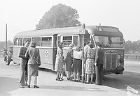 Passengers board a HTM city bus, which is equipped with a wood gas generator on a trailer.