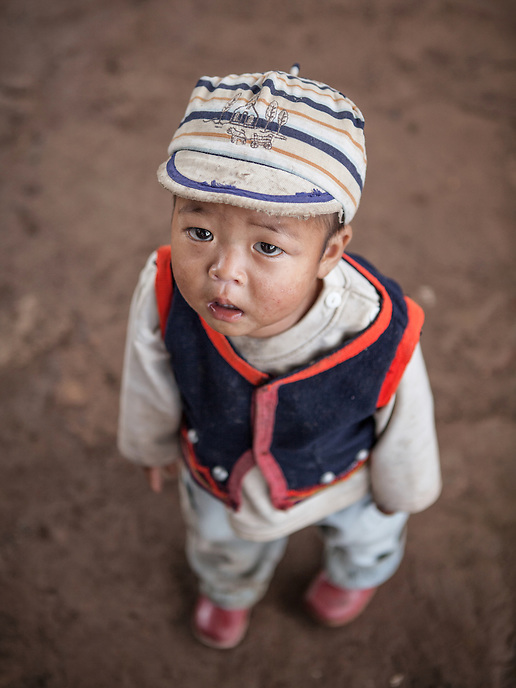 """A Wa young boy dressed in traditional vest in the village of Wengding. The Wa, which literally means """"mountain dwellers"""", is the hilltribe that inhabit the Sino-Burmese. Known as one of the last headhunting tribe until mid-twentieth century, their population in both countries now approximately no more than one million. In the homogenous society of modern China, Wa is one of more than 50 officially state-recognized ethnic minorities. They can be found around the southwestern corners of Yunnan province."""