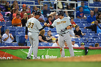 Trenton Thunder manager Al Pedrique (23) fist bumps Tyler Austin (35) after hitting a triple during a game against the Binghamton Mets on August 8, 2015 at NYSEG Stadium in Binghamton, New York.  Trenton defeated Binghamton 4-2.  (Mike Janes/Four Seam Images)