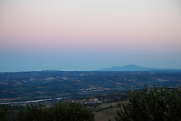 A view of the Tiber valley from Lugnano in Teverina, with the mountains in the direction of Viterbo on the background and the historical center of Alviano nearly in foreground. The photo is taken at the sunrise light of a sunny summer day (in fact, the sun is going to appear on the opposite side of the hill where is located Lugnano historical center).  Digitally Improved Photo.