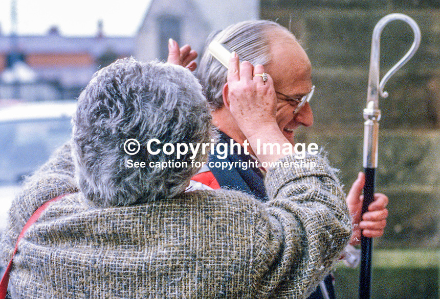 Rt Rev Robin Eames gets his hair brushed just prior to prior to entering St Patrick's Cathedral, Armagh, for his enthronement as Archbishop of Armagh and Primate of All Ireland. April 1986. 19860402RE2.<br /> <br /> Copyright Image from Victor Patterson,<br /> 54 Dorchester Park, <br /> Belfast, UK, BT9 6RJ<br /> <br /> t1: +44 28 9066 1296 (from Rep of Ireland 048 9066 1296)<br /> t2: +44 28 9002 2446 (from Rep of Ireland 048 9002 2446)<br /> <br /> m: +44 7802 353836<br /> <br /> e: victorpatterson@me.com<br /> www.victorpatterson.com<br /> <br /> Please see my Terms and Conditions of Use at www.victorpatterson.com. It is IMPORTANT that you familiarise yourself with them.<br /> <br /> Images used on the Internet must be visibly watermarked i.e. &copy; Victor Patterson<br /> within the body of the image and copyright metadata must not be deleted. Images <br /> used on the Internet have a size restriction of 4kbs and will be chargeable at current<br />  NUJ rates unless agreed otherwise.<br /> <br /> This image is only available for the use of the download recipient i.e. television station, newspaper, magazine, book publisher, etc, and must not be passed on to any third <br /> party. It is also downloaded on condition that each and every usage is notified within 7 days to victorpatterson@me.com<br /> <br /> The right of Victor Patterson to be identified as the author is asserted in accordance with The Copyright Designs And Patents Act (1988). All moral rights are asserted.