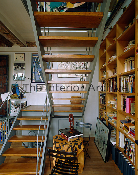 A small reading table and chairs is tucked under the open staircase connecting the upper and lower levels of a library arranged over two floors