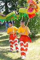 Asian dancers proceed to festival ceremony with pole dragon. Dragon Festival Lake Phalen Park St Paul Minnesota USA