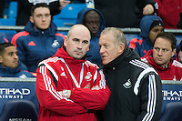 Swansea City Caretaker Manager Alan Curtis chats Performance Psychologist Ian Mitchell whilst they stand in the dugout during the Barclays Premier League Match between Manchester City and Swansea City played at the Etihad Stadium, Manchester on 12th December 2015