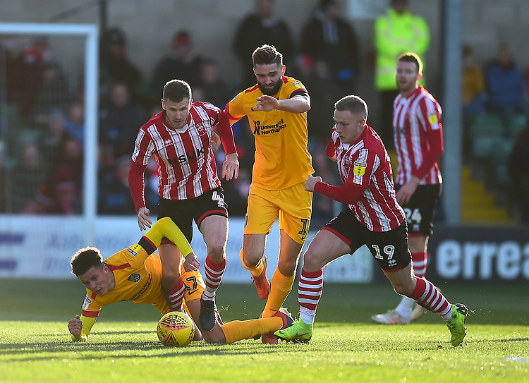 Lincoln City's Michael O'Connor, 2nd left and Danny Rowe, right bring the ball out of defence under pressure from Northampton Town's Shaun McWilliams, left, and Jordan Turnbull<br /> <br /> Photographer Andrew Vaughan/CameraSport<br /> <br /> The EFL Sky Bet League Two - Lincoln City v Northampton Town - Saturday 9th February 2019 - Sincil Bank - Lincoln<br /> <br /> World Copyright © 2019 CameraSport. All rights reserved. 43 Linden Ave. Countesthorpe. Leicester. England. LE8 5PG - Tel: +44 (0) 116 277 4147 - admin@camerasport.com - www.camerasport.com