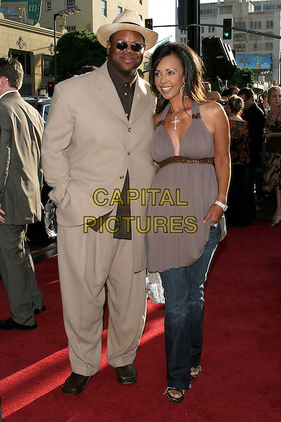 "JIMMY JAM & WIFE LISA.The Los Angeles premiere of ""The Dukes Of Hazzard"".Graumans Chinese Theatre,.Hollywood, 28th July 2005.full length beige taupe suit browm shoes shirt sunglasses grey gray halter neck top jeans crucifix.www.capitalpictures.com.sales@capitalpictures.com.© Capital Pictures."