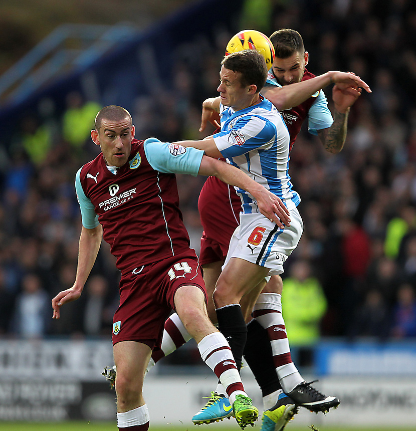 Burnley's Jason Shackell and David Jones jump with Huddersfield Town's Jonathan Hogg<br />