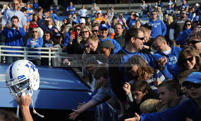 A UK player hoists his helmet in victory to the UK fans' cheers after the University of Kentucky football game against Tennessee at Commonwealth Stadium in Lexington, Ky., on 11/26/11. UK won the game 10-7. Photo by Bob Weaver | Staff