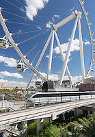 Las Vegas, Nevada.  Monorail Speeds by  High Roller in background.  The High Roller is the world's tallest observation wheel, as of 2015.