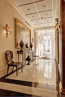 An opulent hallway with gilded ceiling, marble floor and antique furniture.