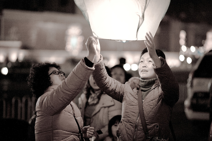 Two chinese women are lighting a paper lantern during the Lantern Festival in  Lanzhou (Gansu province). February 9 2009.
