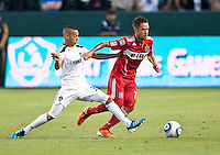 CARSON, CA – July 9, 2011: Chicago Fire midfielder Daniel Paladini (11) between LA Galaxy midfielders Paolo Cardozo (30) and Chris Birchall (8) during the match between LA Galaxy and Chicago Fire at the Home Depot Center in Carson, California. Final score LA Galaxy 2, Chicago Fire FC 1.