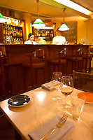 A table set for two with wine glasses and linen napkins and forks at the gastronomic restaurant Eriks Bakficka på Östermalm. The bar with a waitress and a waiter and bar stools in the background Stockholm, Sweden, Sverige, Europe