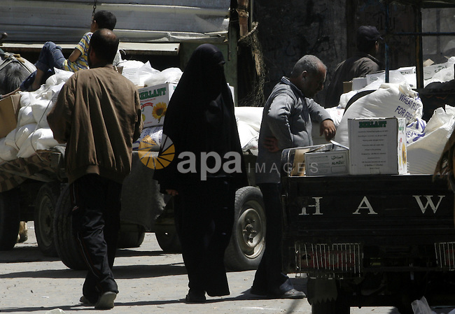 "Palestinians receive monthly food aid from the United Nations Relief and Works Agency (UNRWA) center in the Rafah refugee camp, southern Gaza on May 07, 2012. The UN Agency for Palestinian Refugees (UNRWA) in Gaza launched an appeal for emergency funds to the Palestinian territories of $ 300 million (235 million), The Deputy Chief Commissioner Margo Ellis at the third anniversary of the end of the devastating Israeli operation ""Cast Lead"" in Gaza (27 December 2008-22 January 2009), said the UNRWA. Photo by Eyad Al Baba"