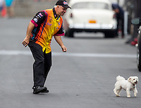 Sep 17, 2016; Concord, NC, USA; NHRA funny car driver Tim Wilkerson chases a dog in the pits during qualifying for the Carolina Nationals at zMax Dragway. Mandatory Credit: Mark J. Rebilas-USA TODAY Sports