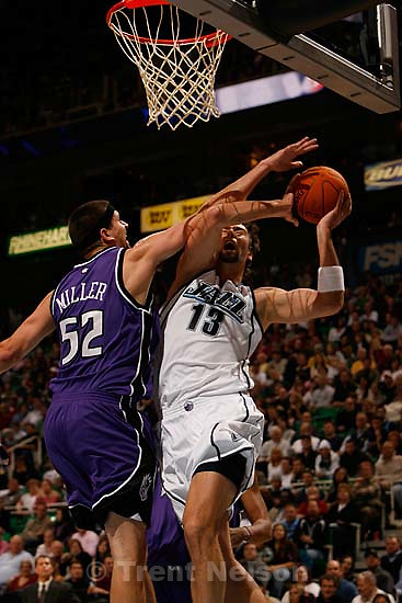 Salt Lake City - Utah Jazz center Mehmet Okur (right, 13), of Turkey, is fouled hard by Sacramento's Brad Miller. Utah Jazz vs. Sacramento Kings NBA basketball.<br />