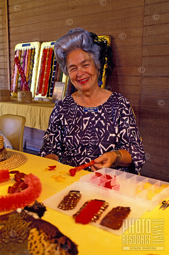 A female kupuna (elder) smiles as she sits at a table with feather lei making materials at Bishop Museum.