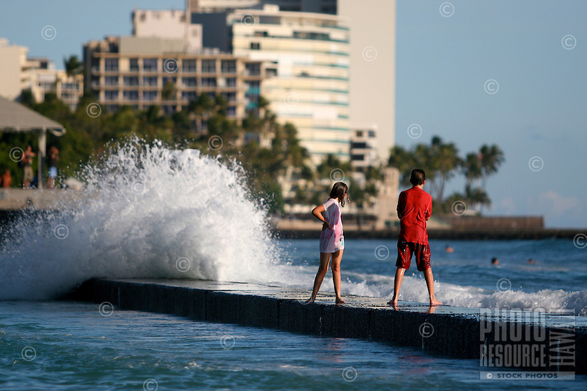 Kids stand on the protective wall as waves splash up along it in downtown Waikiki.