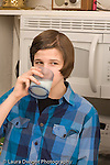 Teenage boy at home in kitchen drinking beverage glass of milk age 14