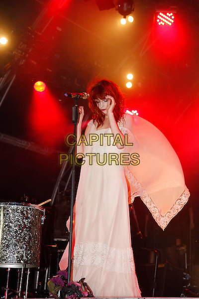 FLORENCE WELCH.Florence and The Machine perform live at Somerset House, London, England..July 15th, 2010.stage concert live gig performance music full length white dress arms hands looking down sheer.CAP/MAR.© Martin Harris/Capital Pictures.