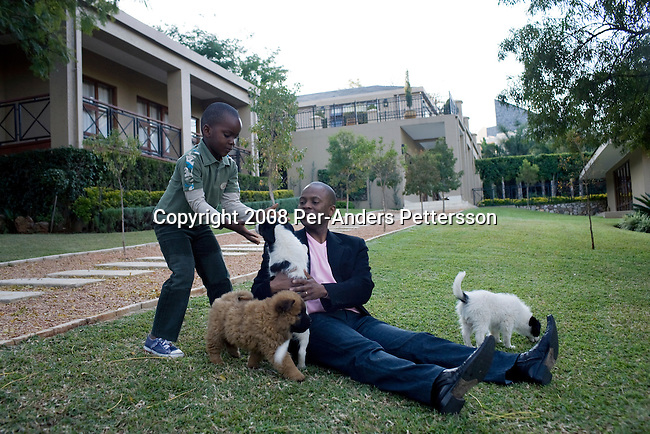 JOHANNESBURG, SOUTH AFRICA - JUNE 20:  Sandile Zungu, age 41, a businessman, plays with his son with his newly bought puppies in the garden outside his huge estate on June 20, 2008 in Bryanstown, South Africa. Known as a whiz kid, he runs ZICO, his own investment company, and he has made millions rands of black empowerment deals in the country. He is an outspoken critic of the ANC regime. He is also a supporter of Jacob Zuma, the ANC leader, and the next inline to become president of South Africa in the general elections on April 22, 2009. (Photo by: Per-Anders Pettersson/Getty Images)...