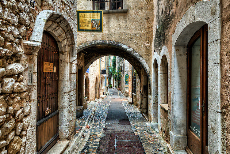 """Early morning shot of an archway and street (the Rue Grande) in Saint Paul de Vence. Over the arch is the """"pontis"""", or bridgework, connecting buildings on opposite sides of the street."""