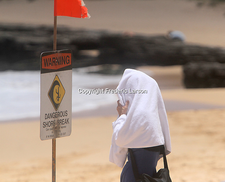 A tourist at Sandy Beach in Hawaii read a warning sign during high-tide that makes for huge breaking waves close to shore.