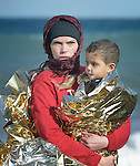 A volunteer holds a refugee boy who just arrived on a beach near Molyvos, on the Greek island of Lesbos, on October 31, 2015.  The boy and his family, part of a boatful of refugees from Turkey, were received by local and international volunteers, then proceeded on their way toward western Europe. The boat was provided by Turkish traffickers to whom the refugees paid huge sums to arrive in Greece. The boy, who got wet on the journey, is wrapped in insulating material to help her keep warm.